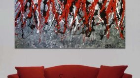 Red and black art above a sofa
