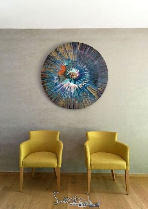 Blue spin art and two mustard yellow chairs