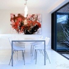 Red and lack abstract painting hung in white dining room