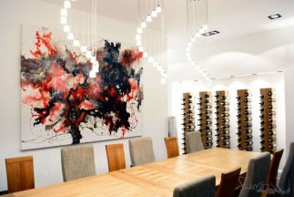 Red and gold art in a dining room with wine cellar