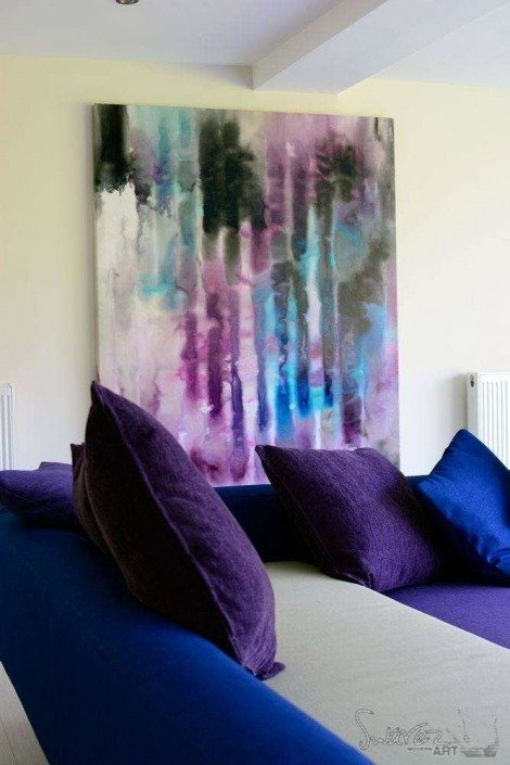 blue painting above a blue and purple sofa