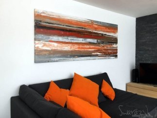Orange and gold painting above a grey sofa
