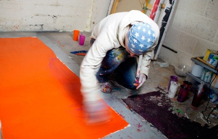 brushing orange paint onto canvas