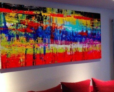art above a red sofa