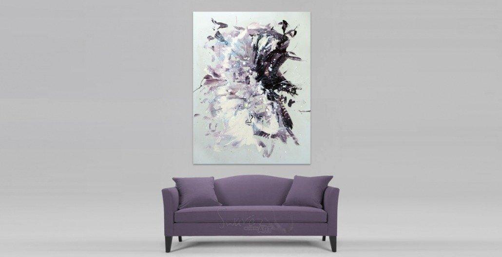Light coloured painting hung above a dusky purple sofa
