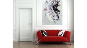 Freefall painting hanging above a red sofa