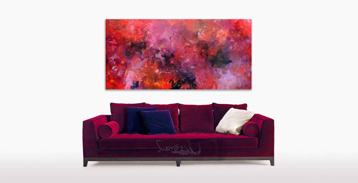 Art hanging above a maroon velour sofa