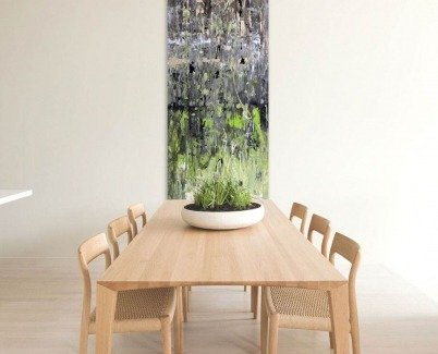 A tall piece of art at the end of a wood dining table