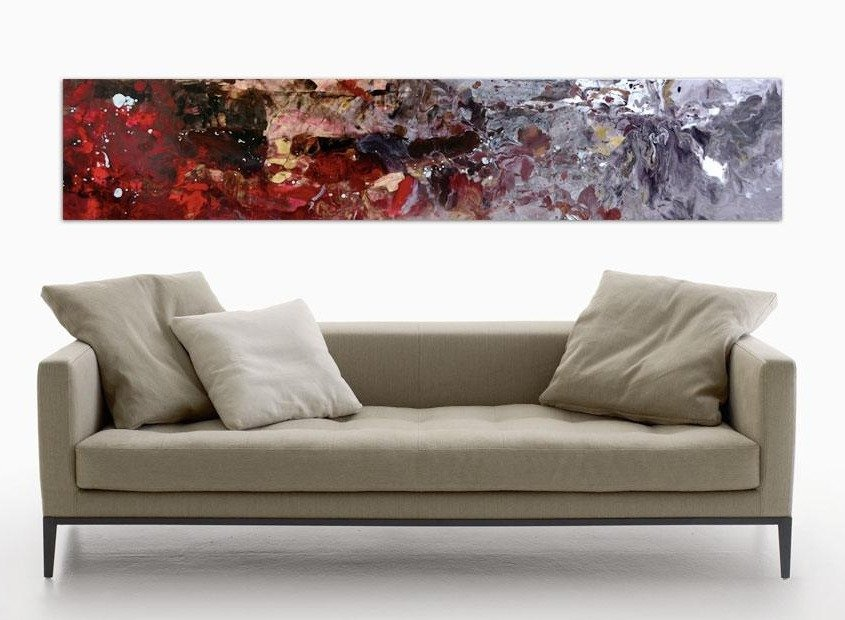 Long beige fabric sofa with a piece of art above it