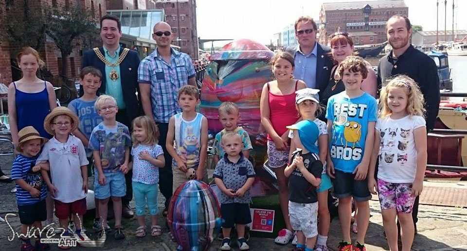 Children gathered round the Swarez Scrumpty sculpture