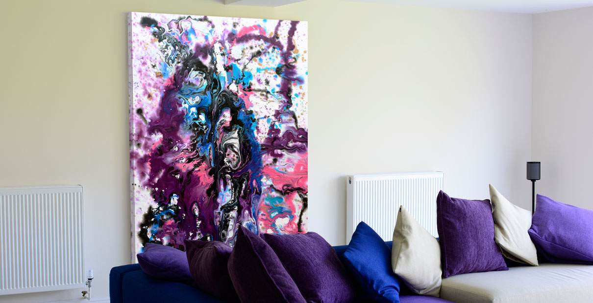 Art called Infinite Possibilities hanging behind a blue and purple sofa