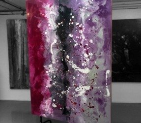 Tall purple painting on a wheeled stand in an art gallery