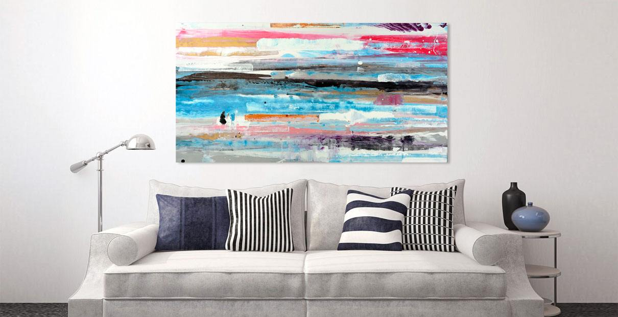 Blue and white art above a sofa