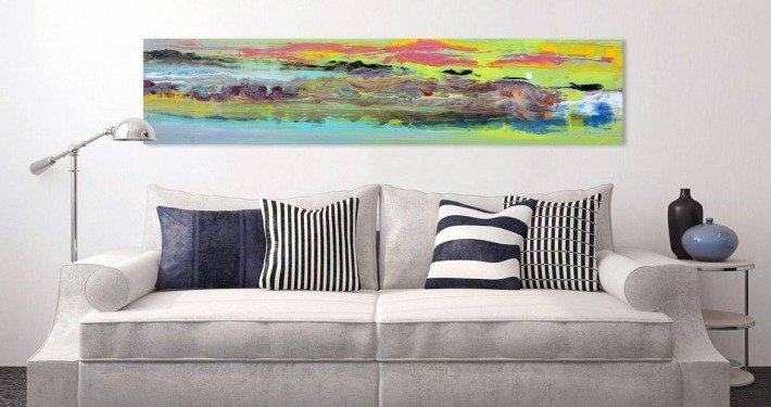 Bright coloured painting above a white sofa