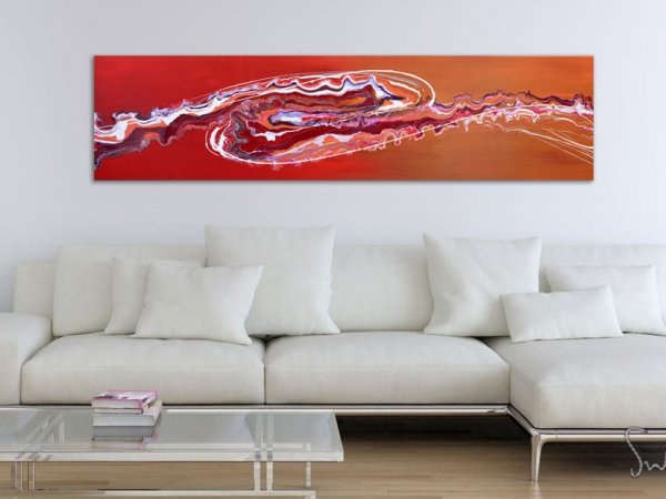 Red art hanging above a white sofa