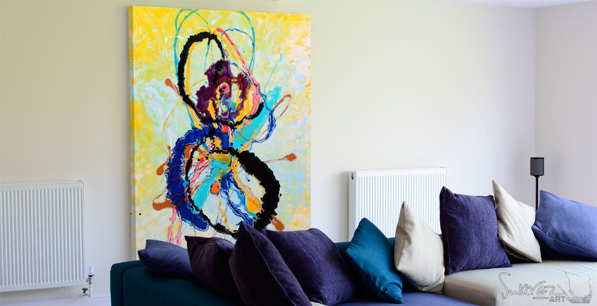 Blue sofa with a large abstract painting behind it