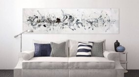 Black and white art above a cream sofa