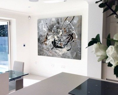 Black and white painting hanging in a modern kitchen