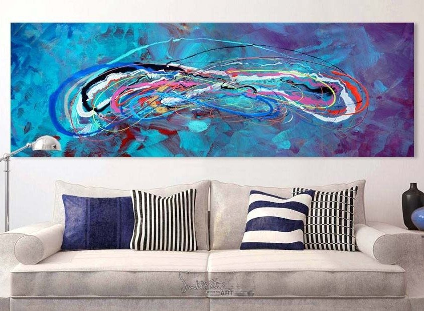 Turquoise and purple art hanging above a beige fabric sofa