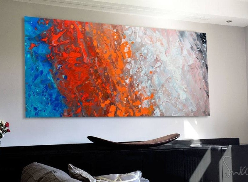 orange-and-blue-art-hanging-above-a-black-console-table