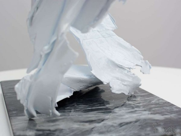 Close up of a white coloured metal sculpture on a marble base