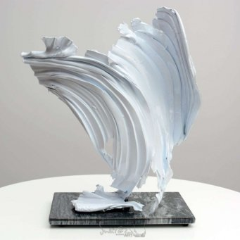 White coloured metal sculpture on a marble base