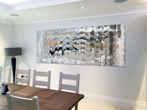 grey and black painting hanging in a light airy dining room
