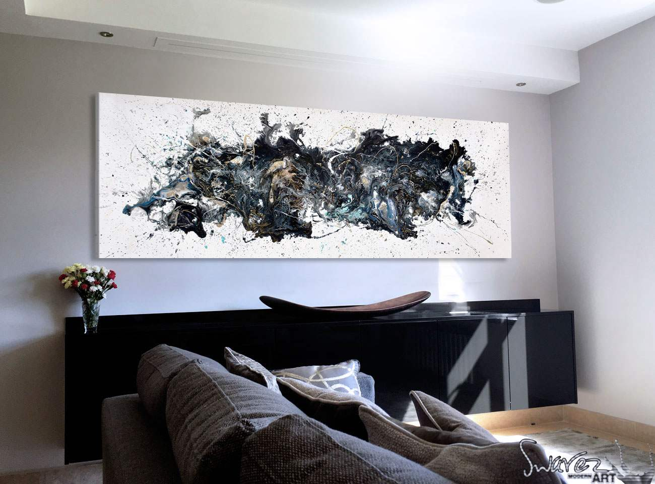 Black and white abstract painting hung on a living room wall