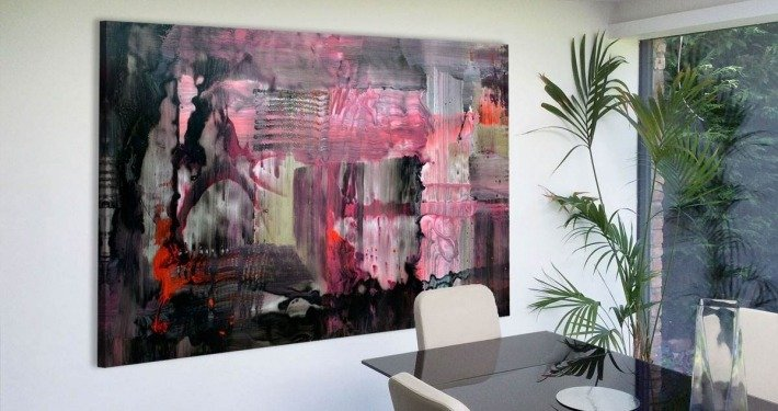 Pink grey and black abstract art in a dining room