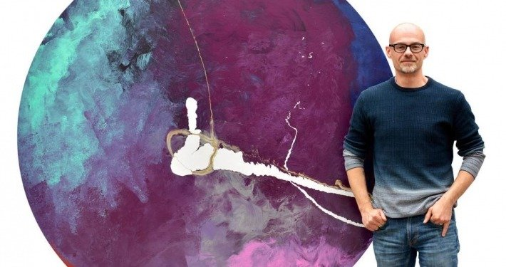 Swarez in front of a large round abstract painting