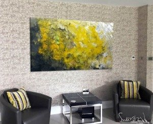 mustard yellow abstract painting and two black chairs